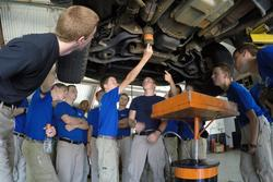 The guys attentively watch as they learn auto maintenance.